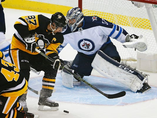 Pittsburgh Penguins' Sidney Crosby (87) can't get his stick on a rebound in front of Winnipeg Jets goalie Connor Hellebuyck (37) in the first period of an NHL hockey game in Pittsburgh, Thursday, Oct. 26, 2017. (AP Photo/Gene J. Puskar)