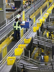 Employees work to fulfill orders at the Amazon Fulfillment Center, in Hebron, on Cyber Monday in 2015.