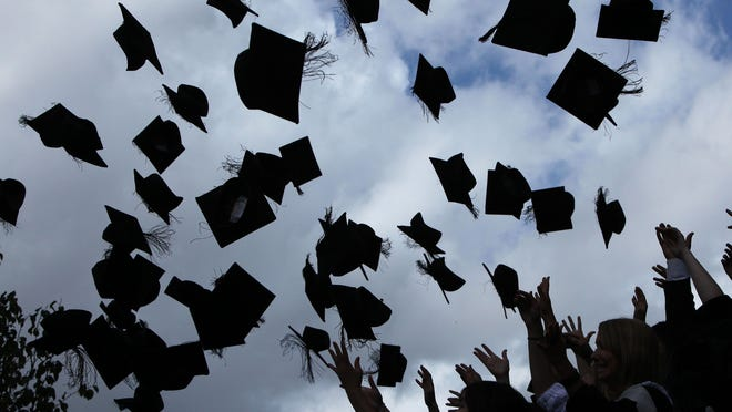 Students throw their mortarboards in the air during their graduation.