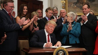 U.S. President Donald Trump signs an executive order as Sen. Rand Paul (R-KY), Vice President Mike Pence, Rep. Virginia Foxx (R-NC) and Secretary of Labor Alexander Acosta look on during an event in the Roosevelt Room of the White House October 12, 2017.