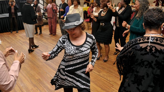 Lois Sims, foreground, joins dozens of women on the dance floor as they break the ice and kick-off the evening at New World Landing Wednesday night during Mamie's 10th Annual Girlfriends' Gathering.