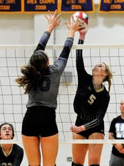 Abilene High's Allison Pierce goes for a kill over Wylie's Bailey Ann Toliver during Tuesday's match at Bulldog Gym.