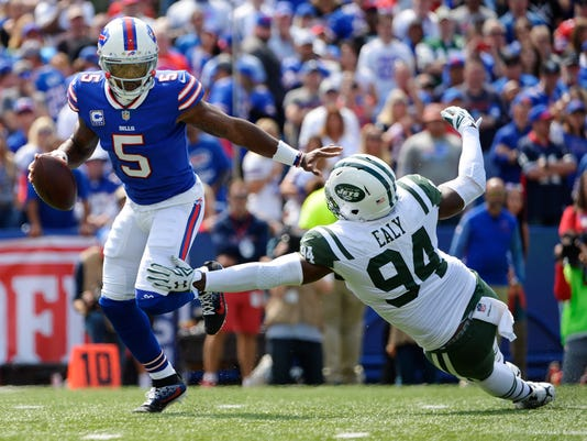 Buffalo Bills quarterback Tyrod Taylor (5) evades a sack by New York Jets' Kony Ealy (94) during an NFL football game Sunday, Sept. 10, 2017, in Orchard Park, N.Y. (AP Photo/Adrian Kraus)