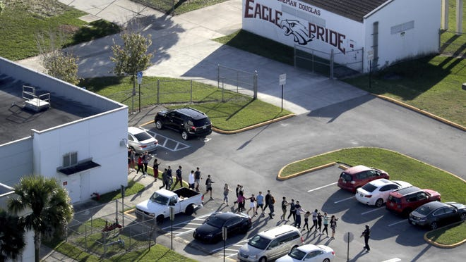 FILE- In this Feb. 14, 2018, file photo, students are evacuated by police from Marjory Stoneman Douglas High School in Parkland, Fla., after a shooter opened fire on the campus. A large Wall Street money manager wants to engage with major weapons manufacturers about their response to the school massacre in Parkland. (Mike Stocker/South Florida Sun-Sentinel via AP, File)