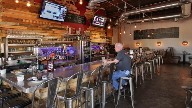 The interior of Salut Kitchen Bar with patron Bob Faith, as seen in Tempe on April, 28, 2014.
