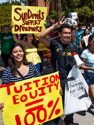 """Korina Iribe, left, a DACA recipient, and Jesus Cisneros, an ASU graduate student and member of the Latino Graduate Student Alliance, (making pitchfork sign) lead the solidarity walk across the Tempe campus, Tuesday, in support of in-state tuition for DACA (Deferred Action for Childhood Arrvivals) students. The solidarity walk participants were asking that the Arizona Board of Regents grant in-state tuition for the so called """"dreamers""""."""