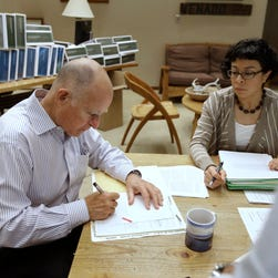 California Gov. Jerry Brown signs one of the hundreds of bills he has left to deal with as Garciela Castillo-Krings, right, his deputy legislative secretary, looks on at his Capitol office in Sacramento, Calif., Friday Oct. 9, 2015.