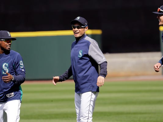 Seattle Mariners' Ichiro Suzuki, center, smiles as he jogs with Dee Gordon, left, and Ryon Healy during a practice on the baseball team's home field Wednesday, March 28, 2018, in Seattle. The team opens play Thursday against the Cleveland Indians. (AP Photo/Elaine Thompson)