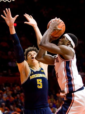 Illinois forward Kipper Nichols (2) shoots defended by Michigan forward D.J. Wilson (5) during the 1st half of U-M's 85-69 loss Wednesday in Champaign, Ill.