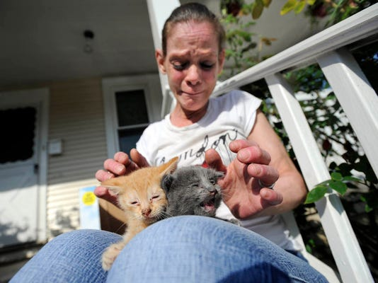 An emotional Christie Logue holds two of the kittens rescued from her Royal St. home in York city from a mattress fire on Friday, April 20, 2012.