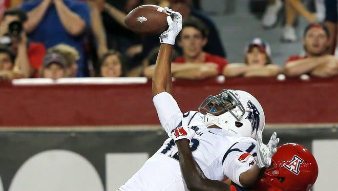 Nevada wide receiver Hasaan Henderson (12) battles with Arizona cornerback Jarvis McCall Jr. (29) during the first half of their game Saturday in Tucson, Ariz.