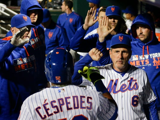 New York Mets' Yoenis Cespedes is greeted in the dugout after scoring against the San Francisco Giants during the third inning of a baseball game, Friday, April 29, 2016, in, New York. (AP Photo/Julie Jacobson)