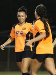 Lady Crushers' Skyylerblu Johnson high-fives teammate Colleen Naden after scoring a goal against the NAPA Lady Rovers in a semifinal match of the Bud Light Women's Soccer League Premier Division Sunday at the Guam Football Association National Training Center. The defending champion Lady Crushers won 5-0.