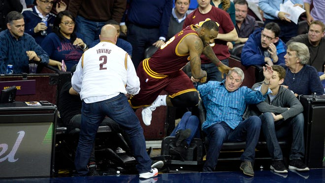 Cleveland Cavaliers forward LeBron James (23) runs back on to the court after colliding with Ellie Day, wife of golfer Jason Day, in the front row during the fourth quarter of a game between the Cleveland Cavaliers and the Oklahoma City Thunder at Quicken Loans Arena.