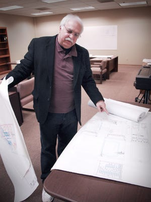 American Gas & Technology CEO Ray Tate looks over architectural drawings of the refurbishment/remodeling of the two buildings at 1270 SE Monmouth Cutoff Road that will house his company.