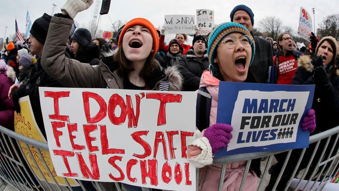 "Demonstrators hold signs during a ""March for Our Lives"" rally in support of gun control, on March 24, 2018."