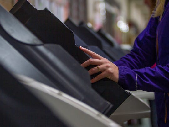 A woman casts her ballot at Fiddler's Canyon Elementary,