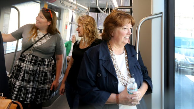 Tammy Monjaras of Landen (right) makes a test run on the Cincinnati Bell Connector. Monjaras works at the Franciscan Media on Liberty St. She is planning to start taking the bus from home and then connecting to the streetcar for the second leg to work. At left are co-workers Kelly Hudson from Sycamore Township and Melody Baron of Taylor Mill.