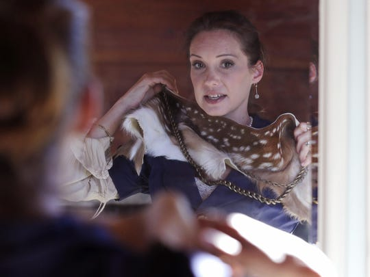 Pam Paquin tries on a fawn scarf and belt at her home in central Massachusetts. Her company, Petite Mort, uses roadkill fur harvested from animal carcasses culled with the help of highway departments and animal control officers.