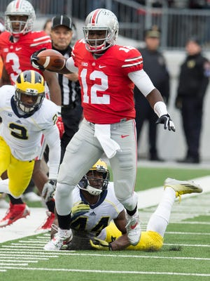 Ohio State Buckeyes quarterback Cardale Jones (12) is tackled by Michigan Wolverines defensive back Delano Hill (44) at Ohio Stadium. Ohio State won the game 42-28.