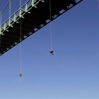 Activists hang from the St. Johns bridge in Portland,