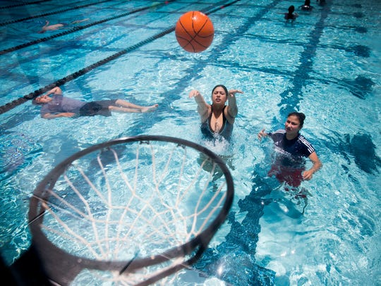 Isabel Ramirez and her friend, Laura Velasquez, play basketball in June 2018 in the lap pool at the new aquatic center at Eagle Lakes Community Park in East Naples.