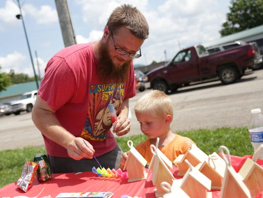 Spencer Shephard and his son, Bo, 3, work on a craft