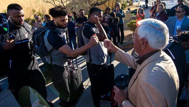 New Mexico State University Chancellor Garrey Carruthers, right, fist bumps men's basketball player Jermaine Haley in front of Aggie fans who came out Wednesday morning to send off the team to Tulsa, Oklahoma, where they take on Baylor on Friday in the NCAA Tournament.