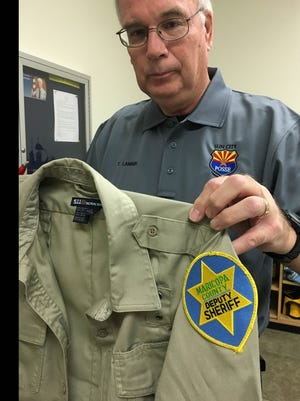 Sun City Posse Lt. Tim Lambin holds his old posse uniform and wears the new one.