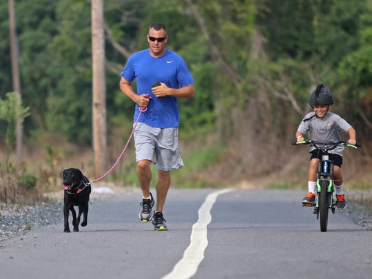 Sgt. Tom Jackson with the New Castle County Police Department runs with his dog Stella and 7-year-old son Matt along the C&D Canal on his morning off from duty.