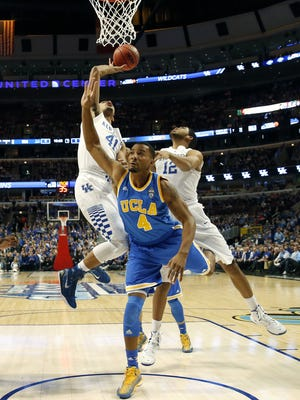 Kentucky forward Trey Lyles (41) shoots over UCLA guard Norman Powell (4) as Karl-Anthony Towns (12) watches for a rebound during the first half of an NCAA college basketball game Saturday, Dec. 20, 2014, in Chicago. (AP Photo/Nam Y. Huh)