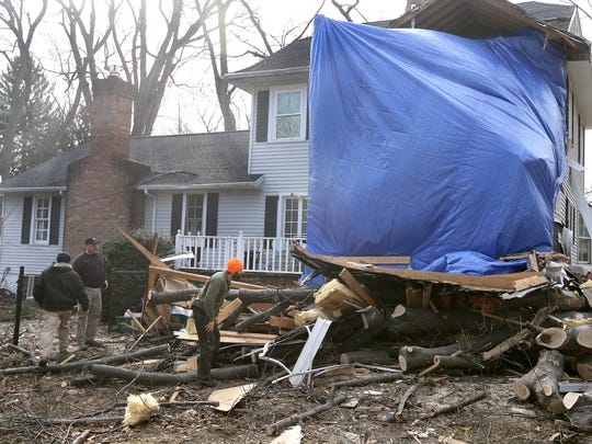Tree removal crews clear debris from this house on the corner of Rock Beach Road and Hillcrest Lane in Irondequoit. The home suffered heavy damage when a large oak tree fell on it during the wind storm in early March.