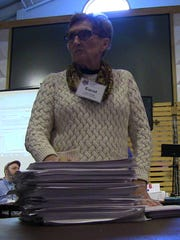 Recount team member Carol Adams stands ready with a stack of ballots Wednesday.