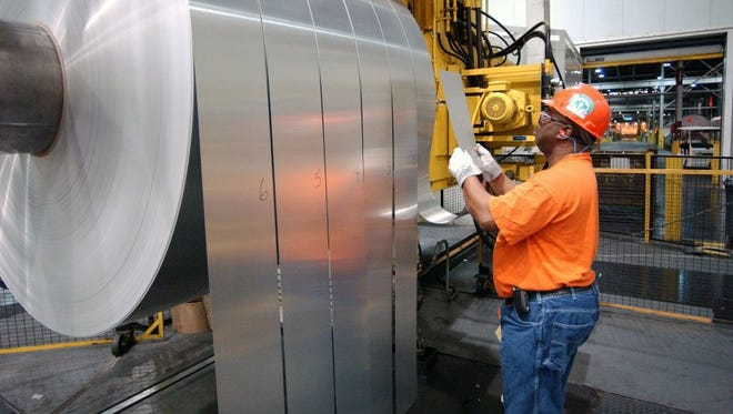 An employee is seen inspecting rolls of finished aluminum in the mill as they came off the last stage of the production line at Alcoa Warrick Operations in Newburgh in April 2006.