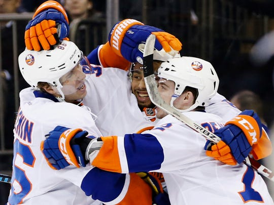 Islanders left wing Nikolay Kulemin, left, and right wing Joshua Ho-Sang, center, celebrate with left wing Anthony Beauvillier (72) after Kulemin scored a tying goal in the third period of a game against the Rangers at Madison Square Garden in New York, Wednesday, March 22, 2017. The Islanders defeated the Rangers 3-2.