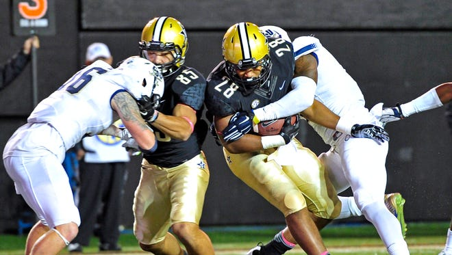 Vanderbilt running back Dallas Rivers (28) powers over Charleston Southern's Demaris Freeman for a touchdown during the second quarter Saturday.