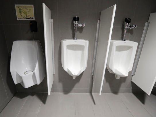 A waterless urinal, left, is shown next to standard