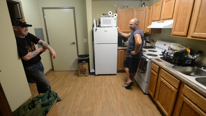 Ed Edict, right, talks with fellow veteran Archie Shaha as Edict gets settled inside his new Veterans Manor apartment. The apartments were built for low-income veterans.