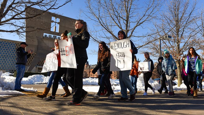 Students from St. John's Preparatory School in Collegeville march across campus after walking out of class Wednesday, March 14, to protest gun violence in schools.