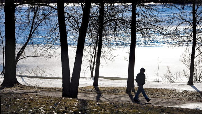 Bright afternoon sunshine highlights open water on the Mississippi River as a man walks down a trail Tuesday, Feb. 14, in Sauk Rapids.