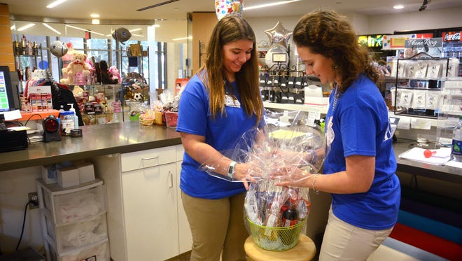 Sisters Victoria Longo, 15 (left), and Elizabeth Longo, then 17, work on a gift basket in the gift shop at Driscoll Children's Hospital in January. Both are members of the hospital's Volunteens program.
