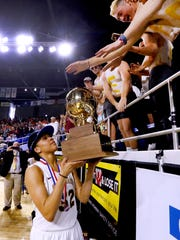 Riverdale senior Brinae Alexander shows off the team's Class AAA state championship trophy.
