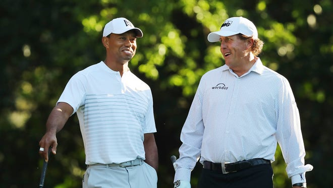 Tiger Woods and Phil Mickelson share a laugh on the 11th tee while playing a practice round for the Masters at Augusta National Golf Club on Tuesday, April 3, 2018, in Augusta, Ga.