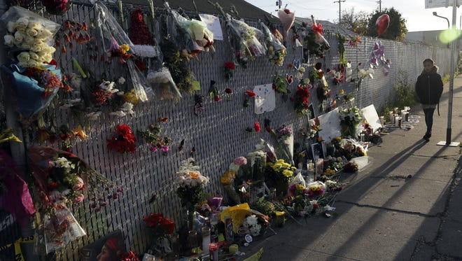 Flowers, pictures and candles adorn a fence at a memorial near the site of the Dec. 2 warehouse fire in Oakland that killed at least 36.