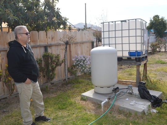 Jose Valera looks at the domestic well at his home. East Porterville residents connecting to municipal water system.