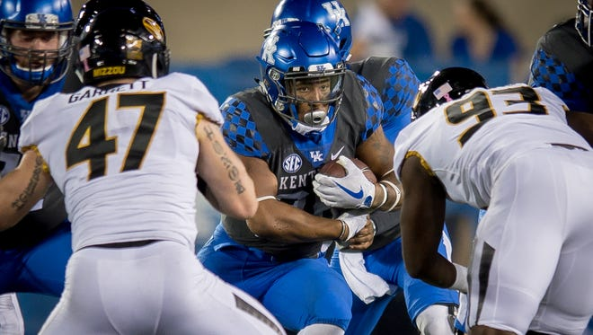 Kentucky Wildcats running back Benny Snell Jr. (26) is tackled by several Missouri Tigers defenders during the game at Kroger Field on the campus of the University of Kentucky in Lexington, Saturday, Oct. 7, 2017.