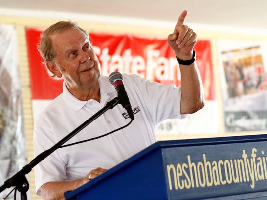 Insurance Commissioner Mike Chaney playfully points out the warning light for wrapping up his speech during his address at the Neshoba County Fair in Philadelphia on Thursday.