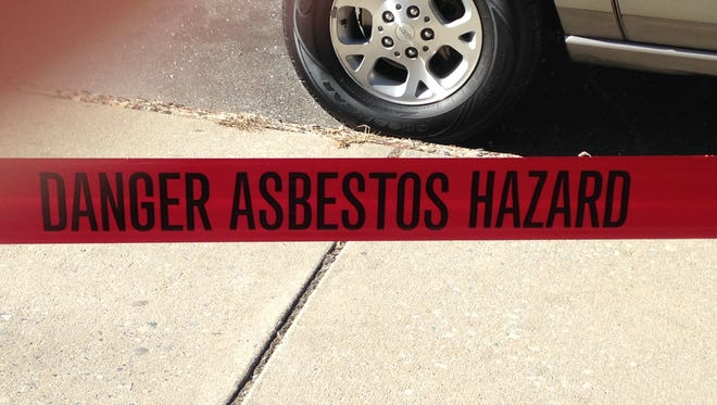 "Before beginning with clearing the rubble Friday morning, Tricon workmen put up tape that reads: ""DANGER ASBESTOS HAZARD."""