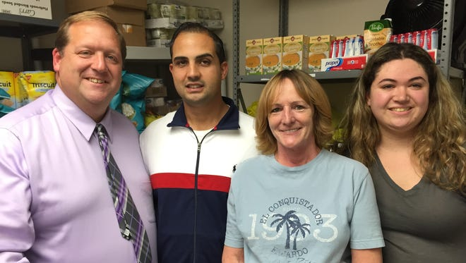 George Hoehmann, left, executive director of the Rockland Independent Living Center, meets in the agency's food pantry with volunteers Antonio Caceres, Bobbi Curti and Sarah Ehrenberg.