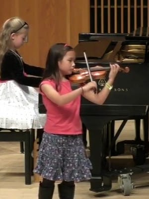 Aber Suzuki Center students perform on piano and violin at a Music of the Masters event.